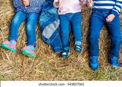 Children in jeans posing in the hayloft
