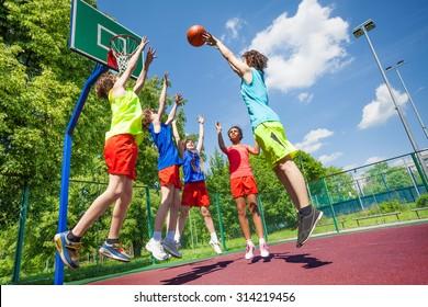 Children jump for ball during basketball game