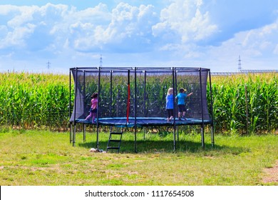 Beautiful Children Jump, Run, Trampolining In Open Jump Trampoline. Garden Big  Trampoline On The