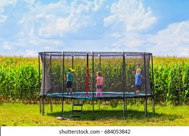 Children jump, run, trampolining in Open Jump Trampoline. Garden big Trampoline on the green grass near the corn field. Outdoor Trampoline with safety net with Zipper entrance.