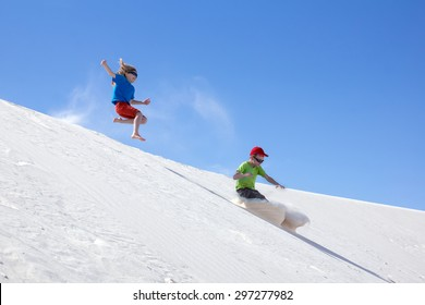 """Children jumping with bare feet down the dune. National Monument """"White Sands"""", New Mexico, United States"""