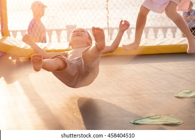 children jumping on trampoline on coast