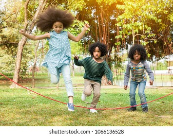 Children jumping over the rope in the park