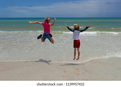 Children jumping over waves on the beach
