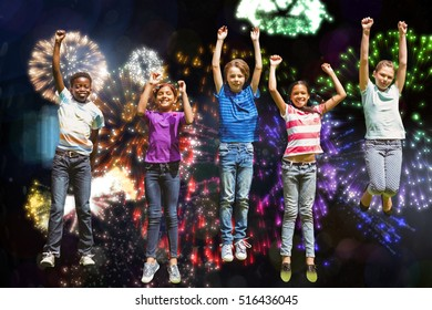 Children jumping at park against colourful fireworks exploding on black background