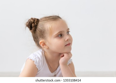 Children and kids concept - Portrait of beautiful little child girl holding her chin on hand and looking up