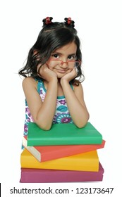 Children / kids education: Cute little Indian girl sitting with pile of books, over isolated white.