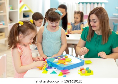 Children kids and teacher playing with constructor on table in kindergarten