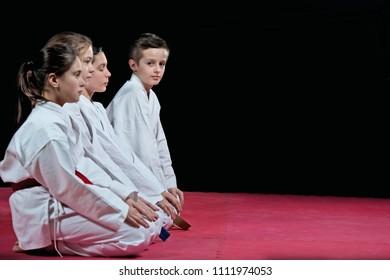 Children in kimono sitting on tatami on martial arts seminar. Selective focus.