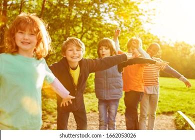 Children in kindergarten balance in the park together in the summer