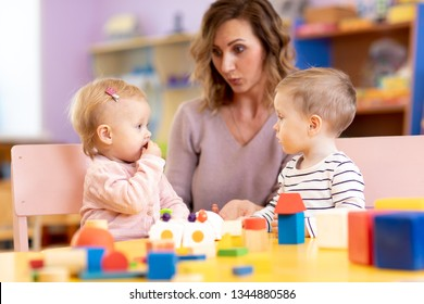 Children in kindergarten. Kids in nursery school. Little girl and boy preschoolers playing at table with teacher