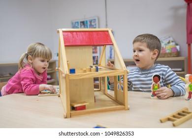 Children in kindergarten making hosue from wooden elements
