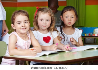 Children in kindergarten with pens and coloring book at a table