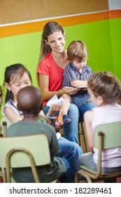 Children in kindergarten sitting in circle and reading book with nursery teacher