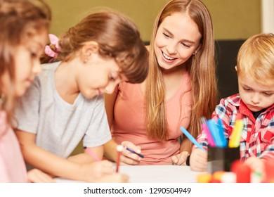 Children and kindergarten teacher paint together in the creative painting class in kindergarten