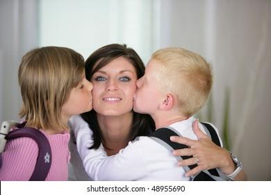 Children kissing their mother goodbye