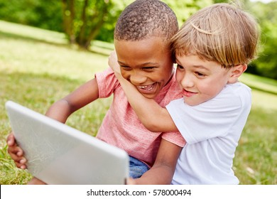 Children with laptop having fun and learning in summer