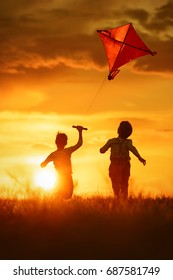 Children launch a kite in the field at sunset