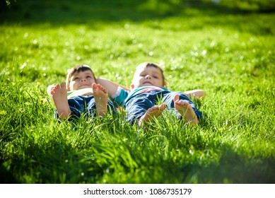 Children laying on grass. Family picnic in spring park. Image of several legs lying on the grass and resting. Relaxation happy childhood friendship concept.