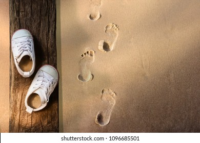 Children Learn Beyond Classroom Concept, Kids Shoes Lay on the Wooden Timber, Sand Beach with Footprint as background, Top view