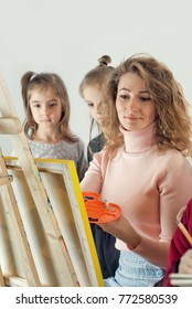 Children learn to draw from the teacher. woman with an easel on a whole background