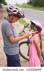 Children learn to ride bicycle in a park on summer day. Teenager boy helping preschooler girl to put on safety helmet. Active outdoor sport for child.