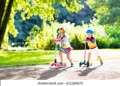 Children learn to ride scooter in a park on sunny summer day. Preschooler boy and girl in safety helmet riding a roller. Kids play outdoors with scooters. Active leisure and outdoor sport for child
