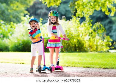 f39a66cc8c861 Children learn to ride scooter in a park on sunny summer day. Preschooler  boy and