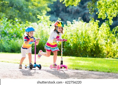Children learn to ride scooter in a park on sunny summer day. Preschooler boy and girl in safety helmet riding a roller. Kids play outdoors with scooters. Active leisure and outdoor sport for child.