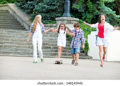 Children learn to ride a skateboard. Children ride on a skateboard mom. Young beautiful mother goes on a skateboard.