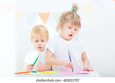 children learning to draw and write at daycare with pencils and pens indoors. girl and boy in preschool age playing together
