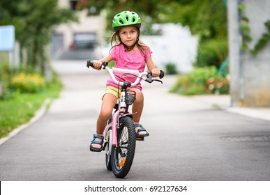 Children learning to drive a bicycle on a driveway outside. Little girls riding bikes on asphalt road in the city wearing helmets as protective gear.