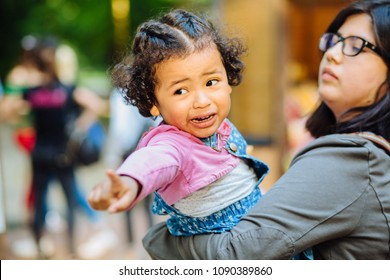 Children learning and family real life concept. Candid moment of latino american mother and dark skinned hispanic toddler daughter crying and pointing somewhere during a walk outdoors.