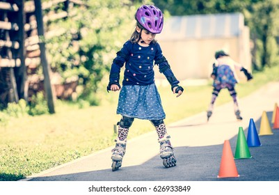 Children learning to roller skate on the road with cones. Twin girls are practising safe roller skating on a home driveway road wearing protective gear - helmets, knee, elbow and hand protectors pads.