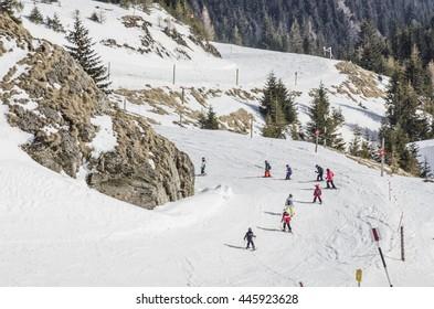 Children learning to ski on a beginners slope in Sinaia, Bucegi Mountains, Romania