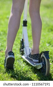 Children legs stand push-bicycle and green sunny grass, rear close-up view