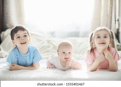 Children lie on the bed next to the newborn baby, little sister. Children's emotions.