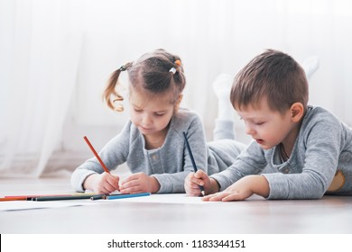 Children lie on the floor in pajamas and draw with pencils. Cute child painting by pencils.
