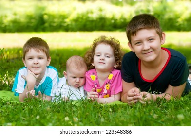 Children lie on the green grass in the park