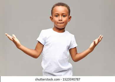 Children, lifestyle and body language. Isolated shot of cool handsome African American little boy having confident look biting lower lip and making gesture with palms, showing he is not afraid