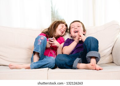 Children listening to music while sitting on a couch