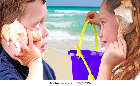 Children listening to shell sounds by ocean