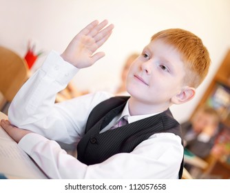 Children listening teacher and boy raising hand for answer during the lesson