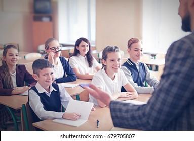 Children listening teacher in classroom at school