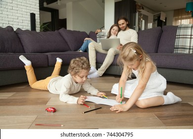 Children little boy and girl having fun on warm floor, boy playing toy car, girl drawing with colored pencils, parents using laptop at home, family leisure together in living room, underfloor heating