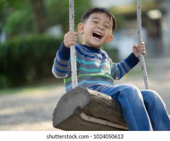 Children, little boy playing swinging wood