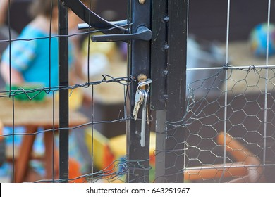 Children locked in playground, behind metal gate and grid.