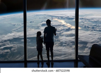 Children look at the Earth through the window. Elements of this image furnished by NASA