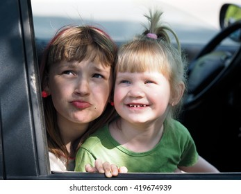 Children look out the car window. Children grimy, satisfied. Portrait of two girls. Concept - travel with children in the car. Children's holiday, happy children.