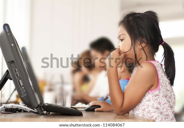 Children looking computer in classroom